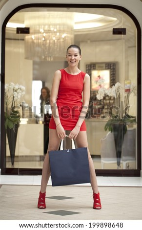Beautiful young woman in red dress walking in the shop