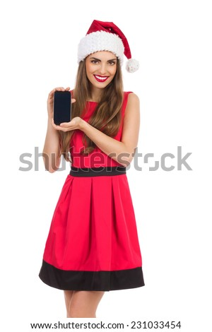 Beautiful young woman in red santa's hat and dress presenting mobile phone. Three quarter length studio shot isolated on white. - stock photo