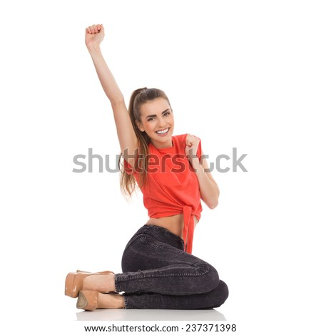 Beautiful young woman in red top, black jeans and high heels sitting on the floor and rising hand. Full length studio shot isolated on white. - stock photo