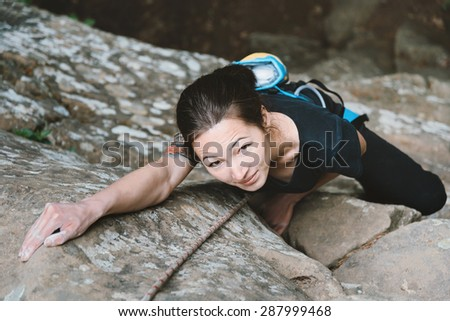 Beautiful young woman in safety equipment climbing on stone rock, top view
