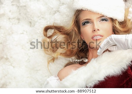 Beautiful young woman in Santa Claus clothes lying in snow. - stock photo
