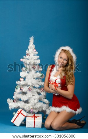 Beautiful young woman in Santa Claus clothes on blue background