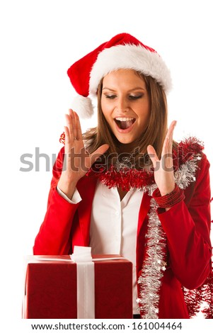 Beautiful young woman in santa claus dress standing isolated over white with christmas presents - stock photo