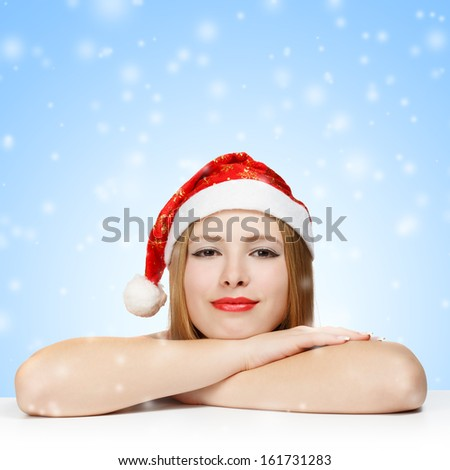 Beautiful young woman in santa claus hat laying on the table on blue background with falling snowflakes