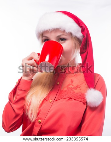 Beautiful young woman in santa claus hat sitting at the table with white cup isolated on white background - stock photo
