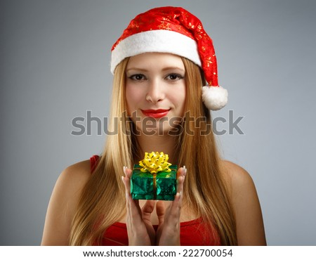 Beautiful young woman in santa claus suit with little gift box on gray background - stock photo