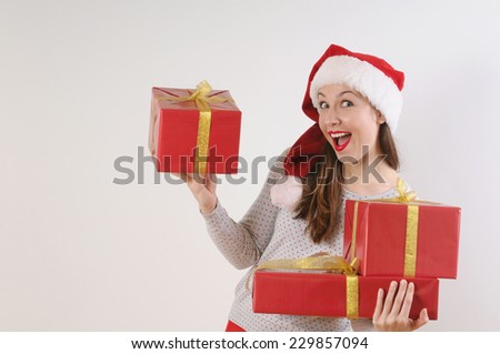 beautiful young woman in santa hat with present boxes for Christmas or New Year holiday on white background - stock photo