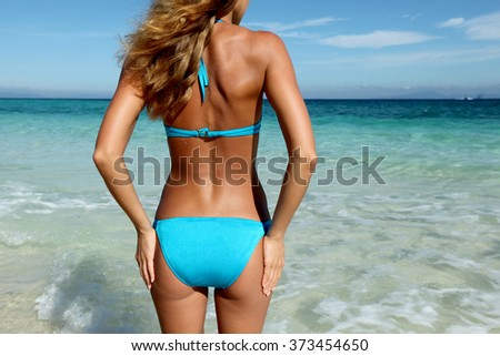 Beautiful young woman in sexy bikini standing at sea beach - stock photo