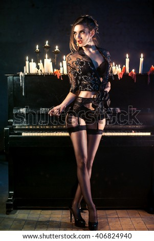 beautiful young woman in sexy lingerie in the dark interior. beautiful sexy girl in lingerie near the piano with candles - stock photo