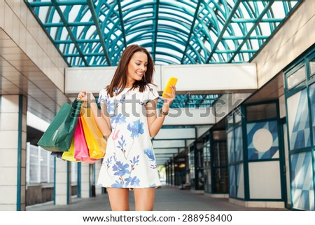 Beautiful young woman in shopping using a mobile phone - stock photo