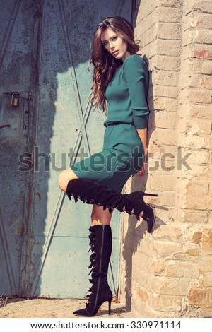 beautiful young woman in short dress and high heels boots against brick wall and old metal door, retro colors, full body shot - stock photo