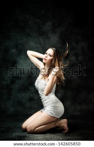 beautiful young woman in short white dress studio dark background - stock photo