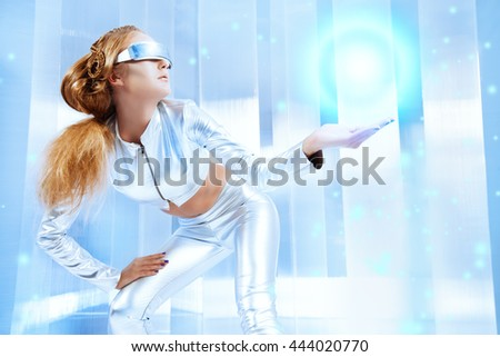 Beautiful young woman in silver latex costume and glasses with futuristic hairstyle and make-up. Sci-fi style. - stock photo