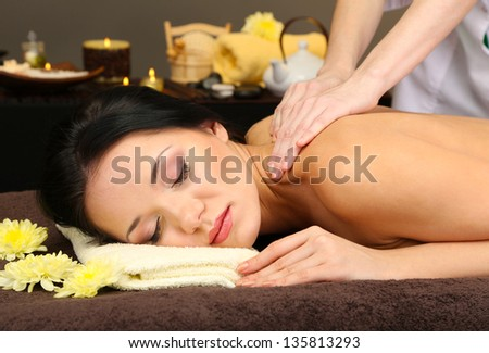 Beautiful young woman in spa salon getting massage, on dark background
