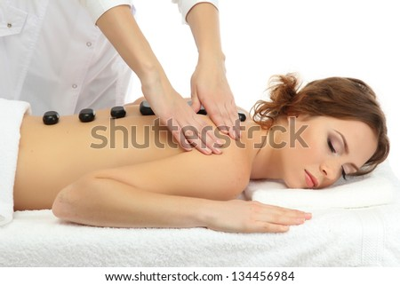 beautiful young woman in spa salon getting massage with spa stones