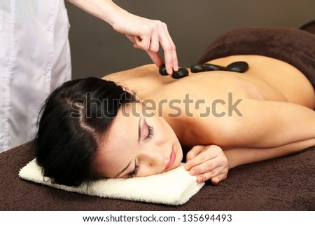 Beautiful young woman in spa salon with spa stones, on dark background