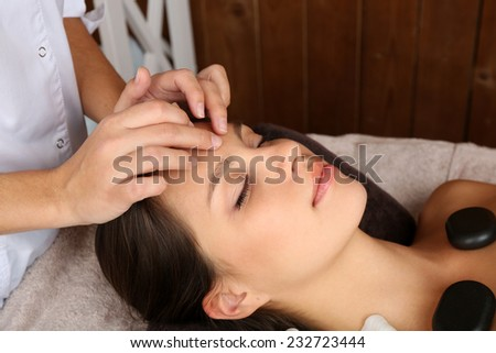 Beautiful young woman in spa salon with spa stones taking head massage - stock photo