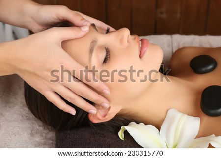 Beautiful young woman in spa salon with spa stones taking head massage