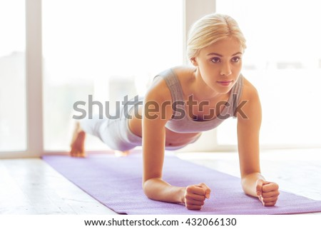 Beautiful young woman in sports wear doing plank exercise on yoga mat - stock photo