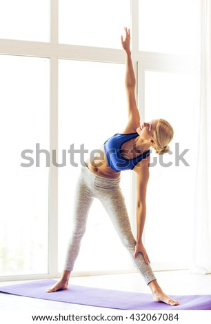 Beautiful young woman in sports wear is doing yoga on mat against windows - stock photo