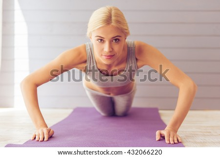 Beautiful young woman in sports wear is looking at camera while doing push ups on yoga mat - stock photo