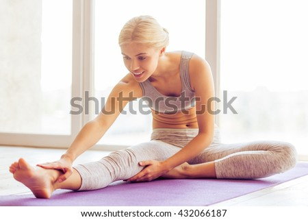 Beautiful young woman in sports wear is smiling while stretching on a yoga mat against window