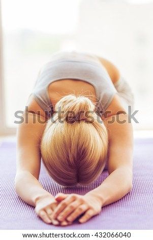 Beautiful young woman in sports wear is stretching on a yoga mat - stock photo