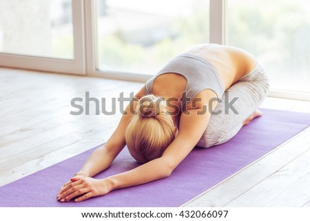Beautiful young woman in sports wear is stretching on a yoga mat