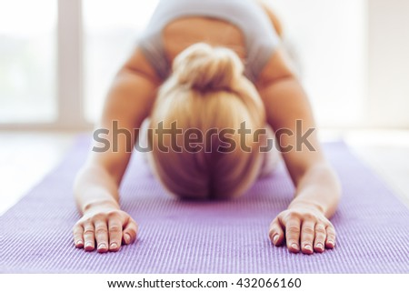 Beautiful young woman in sports wear is stretching on a yoga mat, hands in focus - stock photo