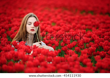 Beautiful young woman in striped dress sitting in a red tulips field at sunset. - stock photo