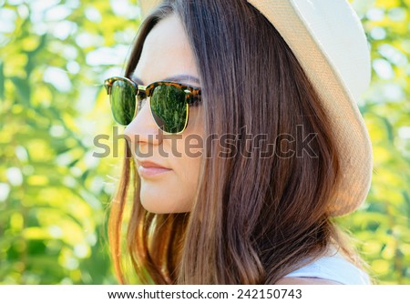 Beautiful young woman in stylish hat and jeans shorts posing. Hipster style. Summer time.