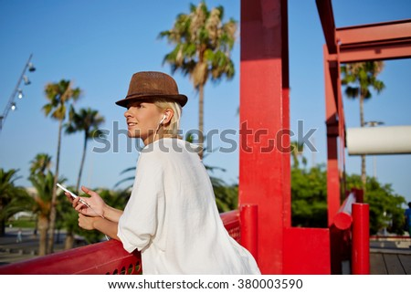 Beautiful young woman in stylish hat enjoying music in headphones via cell telephone while standing on city bridge, attractive female listening radio via mobile phone during rest outside in summer day - stock photo