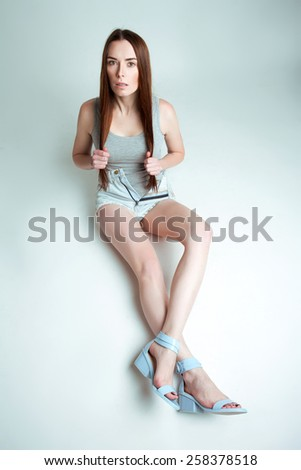 Beautiful young woman in stylish jeans short grey T-shirt and blue shoes posing on a floor in a studio. Fashion pose.   - stock photo