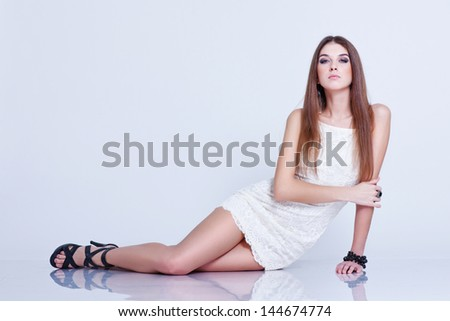 Beautiful young woman in stylish short white dress and black shoes posing on a floor in a studio - stock photo