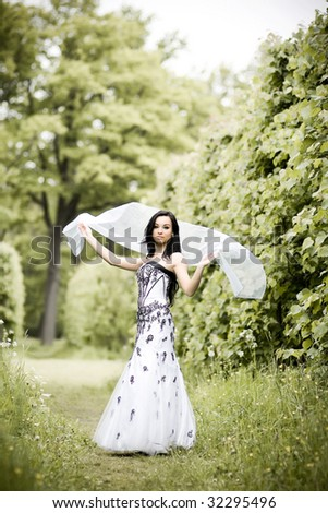 Beautiful young woman in summer park - stock photo
