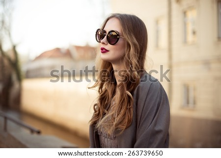 Beautiful young woman in sunglasses in the city - stock photo