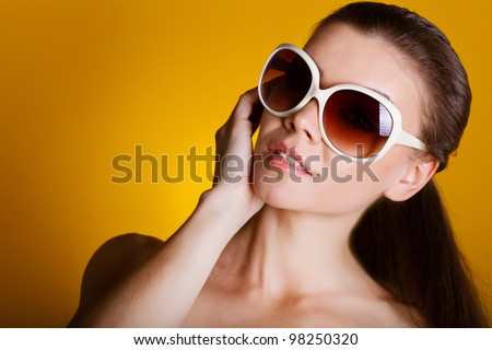 Beautiful young woman in sunglasses isolated on yellow background - stock photo
