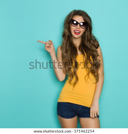 Beautiful young woman in sunglasses, jeans shorts and yellow shirt pointing at copy space and talking. Three quarter length studio shot on teal background. - stock photo