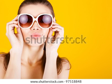 Beautiful young woman in sunglasses kissing you isolated on yellow background - stock photo