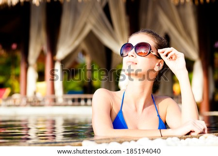 Beautiful young woman in sunglasses with flower in hair smiling in luxury pool - stock photo