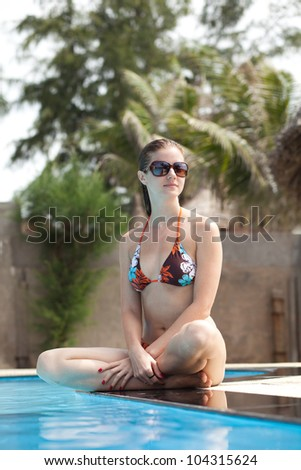 Beautiful young woman in swimsuit and sunglasses sitting on the edge of swimming pool - stock photo