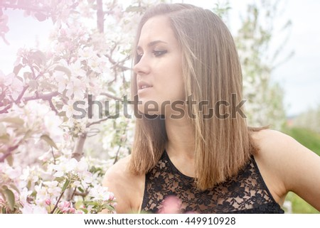 beautiful young woman in the apple garden smelling flower near the apple blossom tree on a warm summer day - stock photo