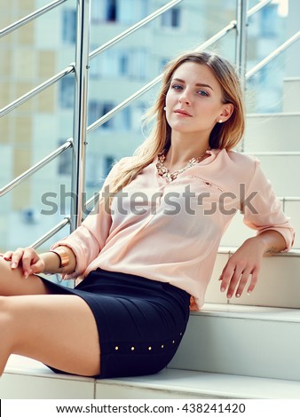 Beautiful young woman in the business center. Sitting on the stairs. Outdoor.