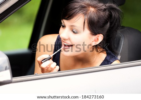 beautiful young woman in the car, with lipstick