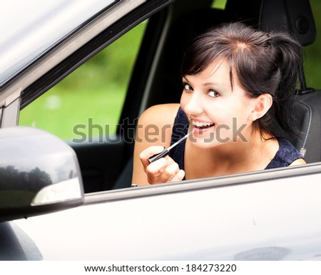 beautiful young woman in the car, with lipstick  - stock photo