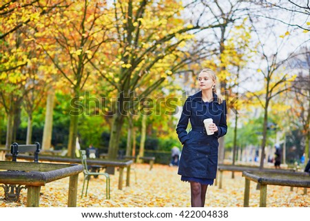 Beautiful young woman in the Luxembourg garden of Paris on a fall day, drinking coffee to go