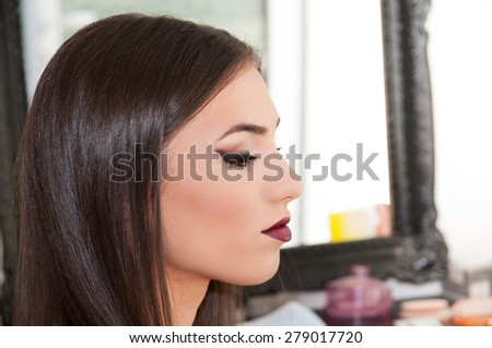 Beautiful young woman in the salon after applying makeup - stock photo