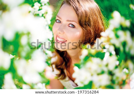 beautiful young woman in the summer park, standing near the apple tree with flowers (focus on the left eye) - stock photo
