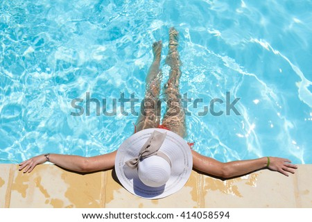 beautiful young woman in the swimming pool on a sunny summer day