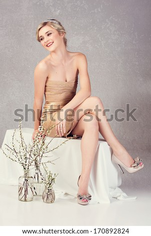 Beautiful young woman in tight gold minidress sitting on studio background  - stock photo